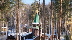 Övervintra landskapet med snö-täckte träd mot bakgrunden av en kristen kyrka efter ett snöfall Frostig solig dag arkivfoton