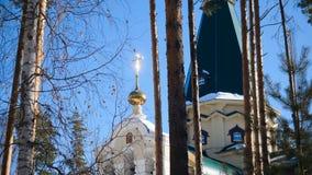 Övervintra landskapet med snö-täckte träd mot bakgrunden av en kristen kyrka efter ett snöfall Frostig solig dag arkivbild