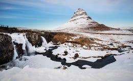 Övervintra landskapet, vattenfall med berget Kirkjufell i Island royaltyfri bild