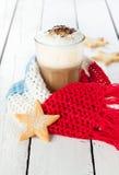 Övervintra lattekaffe i vitt högväxt exponeringsglas med julkakor Arkivfoto