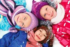 Övervintra lyckliga barn som sledding på vintertid Arkivfoton