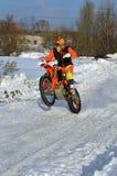 Övervintra motocrossryttaren som rider en wheelie till och med snön Arkivbilder