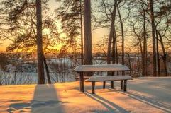 Övervintra platsen, bordlägga, bänken och träd i snön på solnedgången royaltyfria bilder