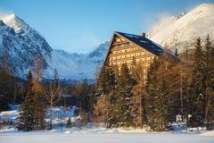 Övervintra sikten av den Strbske Pleso byn med hotellet, barrskogen och snöig maxima Arkivbilder