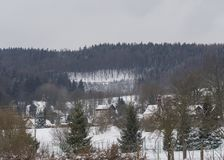 Övervintra sikten på bytravnik med kapell, stuga och träd, s Royaltyfri Foto