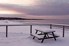 Övervintra sikten till stranden med en bänk som är full av snö Arkivbild