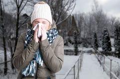 Övervintra sjukdombegreppet med kvinnan som blåser in i servett arkivfoto