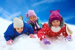 Övervintra snö, lyckliga barn som sledding på vintertid Royaltyfria Bilder