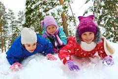 Övervintra, snöa, barn som sledding på vintertid Arkivbild