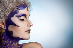 Övervintra ståenden av en flicka med idérikt smink på en ljus bakgrund Lilor - guld- makeup Arkivfoto