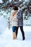 övervintra ståenden av lyckliga par som har gyckel i snöig skog royaltyfri foto