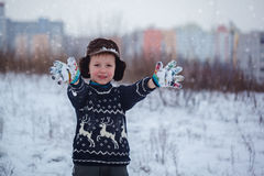 Övervintra ståenden av pojken för den lilla ungen som bär en stucken tröja med deers, utomhus under snöfall Arkivbilder
