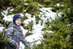 Övervintra ståenden av ungepojken i färgrik kläder, utomhus under snöfall Aktiv outoorsfritid med barn i vinter på förkylning s Royaltyfri Foto