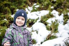 Övervintra ståenden av ungepojken i färgrik kläder, utomhus under snöfall Aktiv outoorsfritid med barn i vinter på förkylning s Royaltyfria Bilder