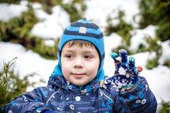 Övervintra ståenden av ungepojken i färgrik kläder, utomhus under snöfall Aktiv outoorsfritid med barn i vinter på förkylning s Arkivbild