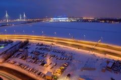 Övervintra staden på natten, den guyed bron, den fryste floden, fotbollstadion Arkivfoto