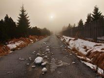 Övervintra stormigt väder i berg, mörka snöig moln, kallt insnöat himlen. Vägen som täckas av snö och is. Häftklammermatareasfalt Arkivfoton