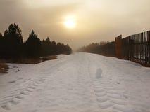 Övervintra stormigt väder i berg, mörka snöig moln, kallt insnöat himlen. Vägen som täckas av snö och is. Häftklammermatareasfalt Arkivfoto