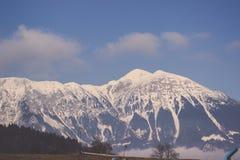 Övervintra toppiga bergskedjan som täckas i snö under klar himmel och moln arkivbild