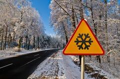 Övervintra vägen som kör till och med snöig skog, varningstecknet Royaltyfri Bild