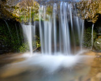 Övervintra vattenfallet i en skog arkivfoton