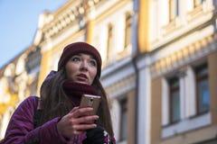 Övervintrar bärande lilor för nätt brunettflicka laget, hatt, och halsduken som går vid den europeiska gatan på vintern, gör foto Royaltyfri Fotografi