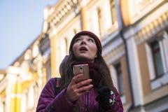Övervintrar bärande lilor för nätt brunettflicka laget, hatt, och halsduken som går vid den europeiska gatan på vintern, gör foto Royaltyfri Bild