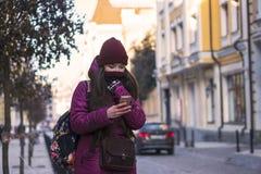 Övervintrar bärande lilor för nätt brunettflicka laget, hatten och halsduken som går vid den europeiska gatan på vintern som slås Arkivfoto