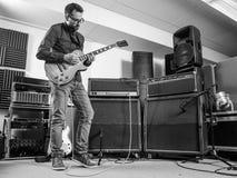 Övning av hans elektriska gitarr i ett driftstopprum Arkivbild