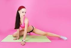 övning Den idrotts- idrottskvinnan sträcker hennes ben genomkörare Arkivfoto