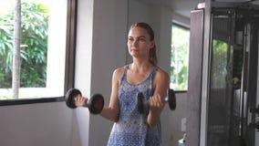 Övning för hantel för konditionkvinna utbildande i idrottshall o 3840x2160 arkivfilmer
