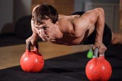 Övning för liggande armhävning för styrka för idrottshallmanliggande armhävning med Kettlebell i en genomkörare royaltyfria bilder