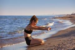 Övning för Pilates yogagenomkörare som är utomhus- på stranden Arkivfoto