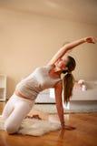 Övning för ung kvinna hemma arkivfoton