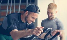 Övning för ung man på stationära cyklar i konditiongrupp royaltyfri fotografi