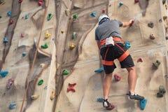 Övning för ung man vaggar klättring på den konstgjorda väggen inomhus royaltyfri bild