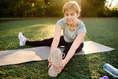 Övning för yoga för mogen kvinna övande utomhus- eller görakondition fotografering för bildbyråer