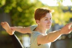 Övning för yoga för mogen kvinna övande utomhus- på stranden nära floden royaltyfri bild