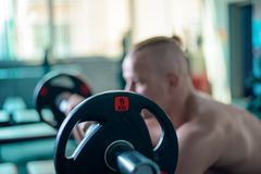 Övningar med en skivstång i idrottshallen, stark manlig modell för sport royaltyfria foton