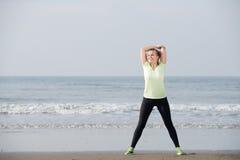 Övningskvinna som ler på stranden Royaltyfri Foto