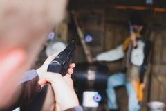 Övningsskottlossning med ett gevär Att skjuta med ett gevär i en gyckel parkerar Första personskytt som siktar i målet Militär be royaltyfri fotografi