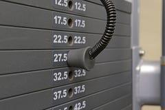 Övningsutrustning - kugge av viktplattor i idrottshall Arkivfoto