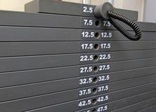 Övningsutrustning - kugge av viktplattor i idrottshall Royaltyfri Bild