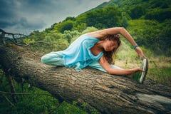 Övningsyoga för ung kvinna som är utomhus- på enormt grymt träd på monteringen fotografering för bildbyråer