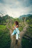 Övningsyoga för ung kvinna som är utomhus- på enormt grymt träd på monteringen royaltyfri foto
