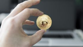 Övre bild för slut av en hand för man` som s rymmer ett guld- mynt av bitcoin mot en bärbar dator i bakgrunden Bitcoin är ett cry Arkivfoto