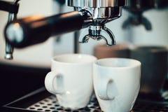 Övre bild för slut av espresso som häller in i vita koppar Arkivbild