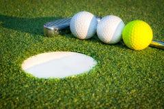 Övre bild för slut av golfhålet med bollar och putt Arkivbild
