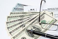 Övre bild för slut av pengar, $100 räkningar, formen W-9, exponeringsglas och en penna Arkivbild