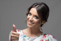 Övre gest för lycklig säker ursnygg skönhetvisningtumme som ler på kameran Royaltyfri Bild